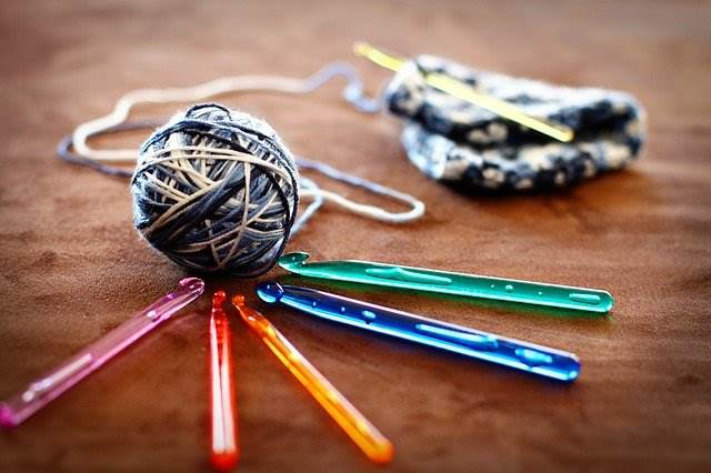 Crochet hooks in a variety of colors are shown next to a ball of yarn and crochet project