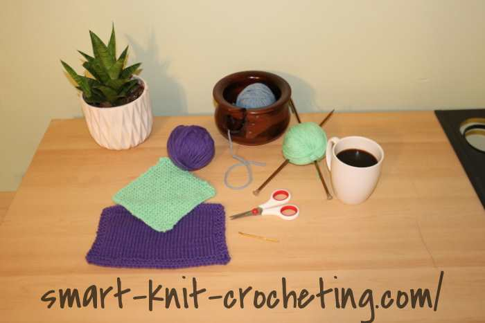 A desk with an assortment of knitting tools and yarns